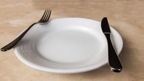 有叉子的空白的白色在大理石石表上的板材和刀子 免版税库存图片
