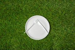 有叉子的空的说谎在草的板材和刀子 JPG 免版税图库摄影