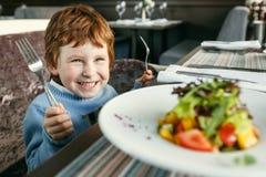 有叉子的红发男孩吃沙拉的 库存照片