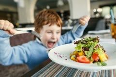 有叉子的红发男孩吃沙拉的 免版税库存照片