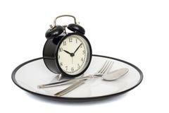 有叉子的黑在板材的闹钟和刀子 查出在白色 吃时间 减重或饮食概念 免版税库存照片