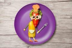 有叉子的滑稽的厨师由菜做成在板材 免版税库存照片
