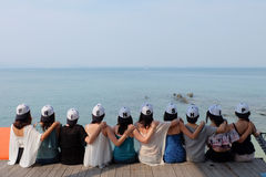 有友谊盖帽的妇女朋友一起坐拥抱蓝色海天空 库存图片