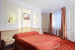 有双人床的简单的卧室与红色亚麻布,隆重 免版税库存照片