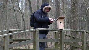 有双筒望远镜和片剂个人计算机的鸟类学家在鸟笼附近 股票视频