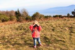 有双筒望远镜旅行的小游人在山 免版税图库摄影