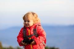 有双筒望远镜旅行的小游人在山 免版税库存照片