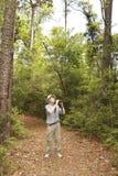 有双筒望远镜的人鸟的监视人在森林足迹的 免版税图库摄影