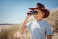 有双筒望远镜的儿童探险家在海滩 免版税库存图片