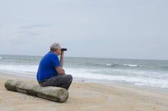 有双筒望远镜的前辈在海滩 免版税库存图片