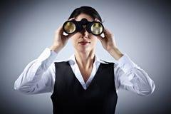 有双筒望远镜的女商人。 库存图片