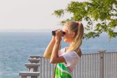 有双筒望远镜的女孩在手中 免版税库存图片