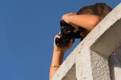 有双筒望远镜的女孩在监视 免版税库存照片