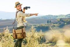 有双筒望远镜的妇女远足者在托斯卡纳指向某事的 免版税图库摄影