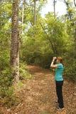 有双筒望远镜的妇女鸟的监视人在森林足迹的 图库摄影