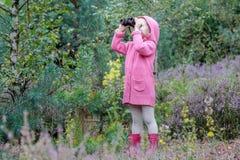 有双筒望远镜的小女孩鸟的监视人在夏天森林里的 库存照片