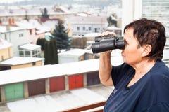 有双筒望远镜的资深妇女 免版税库存照片