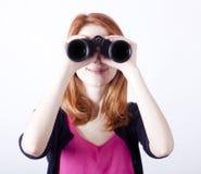 有双筒望远镜的青少年的红头发人女孩 库存照片