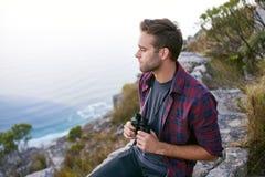 有双筒望远镜的年轻人在与海洋贝耳的一个岩石山腰 免版税库存照片