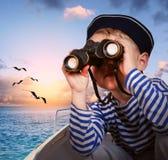 有双筒望远镜的水手男孩在小船 免版税库存图片