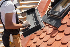 有双重斜坡屋顶的房屋的窗口的设施在红色瓦片一个新的屋顶的  库存照片