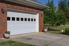 有双重车库门、红砖和罐的普通房子花 免版税库存图片