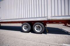 有双重轨的白色大船具半拖车在路转动 免版税库存照片