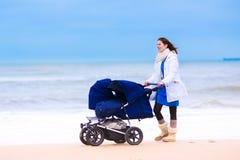 有双婴儿推车的母亲在海滩 库存图片