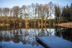 有反射在湖水表面,秋天的树的一座桥梁 库存照片