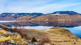 有反射安静的表面上的周围的山的Kamloops湖 免版税库存图片