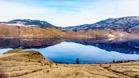 有反射安静的表面上的周围的山的Kamloops湖 免版税库存照片