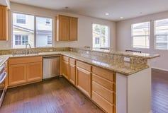 有反射性地板和花岗岩的明亮的厨房 免版税库存照片