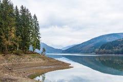 有反射的树的高山湖和美丽的多云天空在秋天 免版税库存照片
