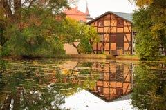有反射的老房子在池塘 库存图片