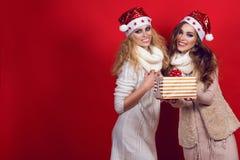 有发光的两个华美的女朋友微笑佩带的圣诞老人帽子并且温暖给当前箱子的羊毛围巾 库存图片