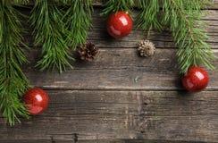 有发光的中看不中用的物品的常青冷杉枝杈和在白色木背景的杉木锥体 免版税图库摄影