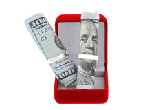 有发光的圆环和美元的一个红色天鹅绒圆环箱子 免版税库存照片