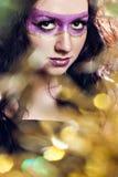 有发光的极端紫罗兰色金子构成的妇女 库存照片
