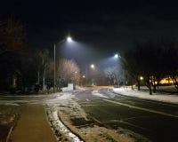 有发光的街灯的冰冷的路 免版税库存图片