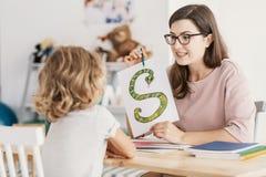 有发展问题的一个孩子的一个专业语言矫治者在会议期间 拿着蛇的支柱海报的家庭教师  免版税库存照片