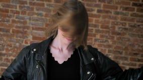 有发烟性眼睛的年轻性感的女孩是跳舞,摇头,中坚分子,砖背景 影视素材