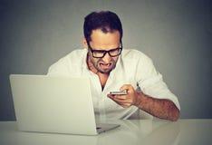 有发短信在手机的膝上型计算机的沮丧的人 免版税图库摄影