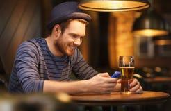 有发短信在酒吧的智能手机和啤酒的人 免版税库存照片
