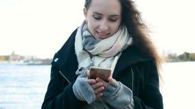 有发短信,使用手机智能手机的美丽的长的头发的俏丽的女孩户外 股票视频