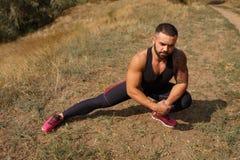 有发茬的一个坚强的肌肉人经过舒展改进灵活性在被弄脏的自然本底 免版税库存图片