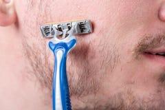 有发茬的帅哥在他的面孔拿着一把剃刀在他的面颊 免版税库存图片