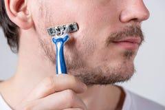 有发茬的帅哥在他的面孔拿着一把剃刀在他的面颊 库存照片