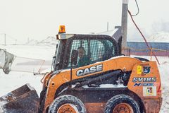 有取消雪的除雪机的拖拉机在大雪期间 图库摄影