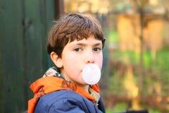 有口香糖泡影关闭的青春期前的英俊的男孩counrty po 免版税库存照片