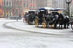 有古板的教练的马支架在空的正方形的降雪下在欧洲 冬天旅行背景 免版税库存照片